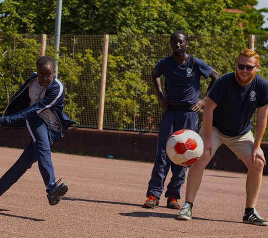 Young people playing football with Sport 4 Life