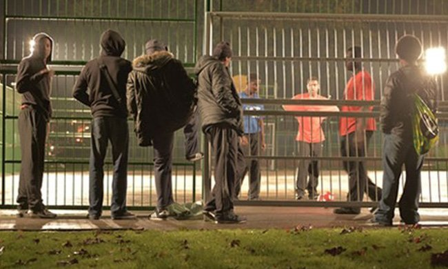 young people standing by gated football pitch