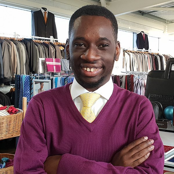 happy young person in suit shop