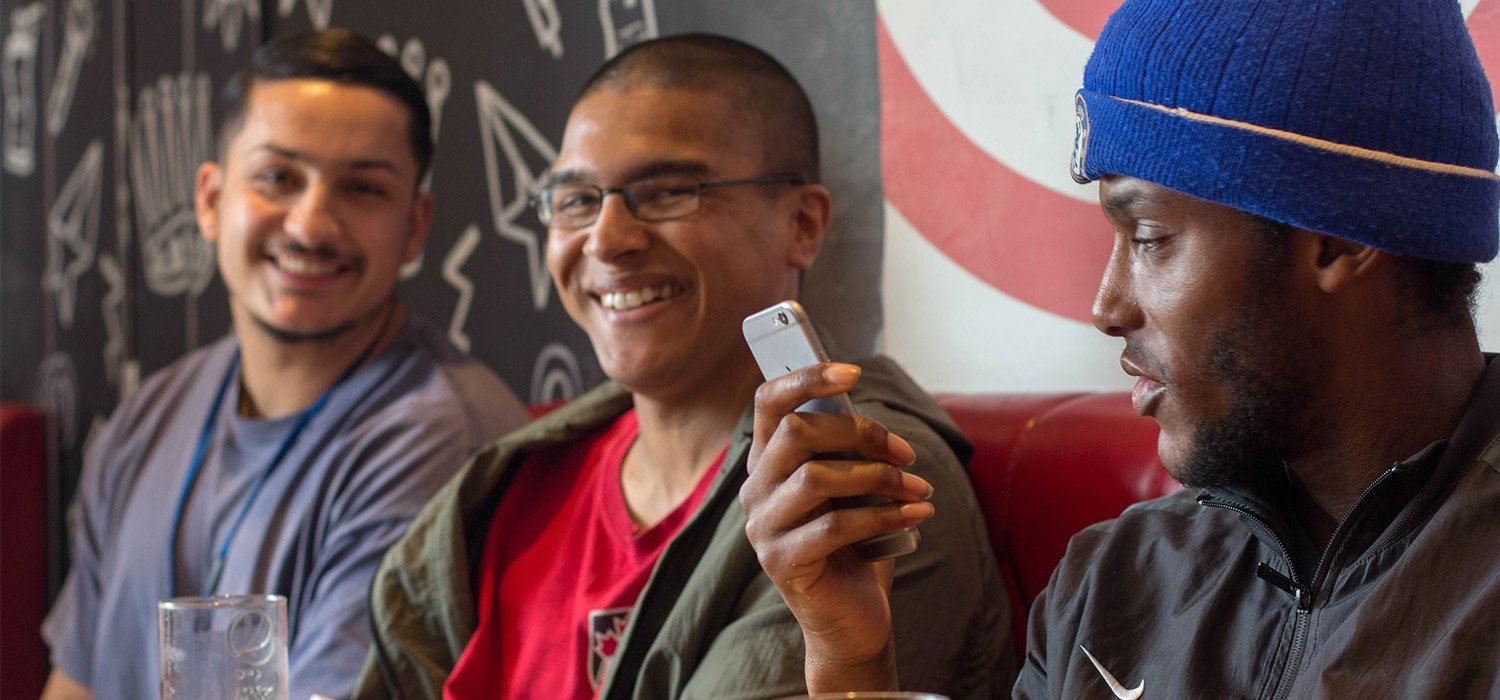 Young people laughing and looking at phone